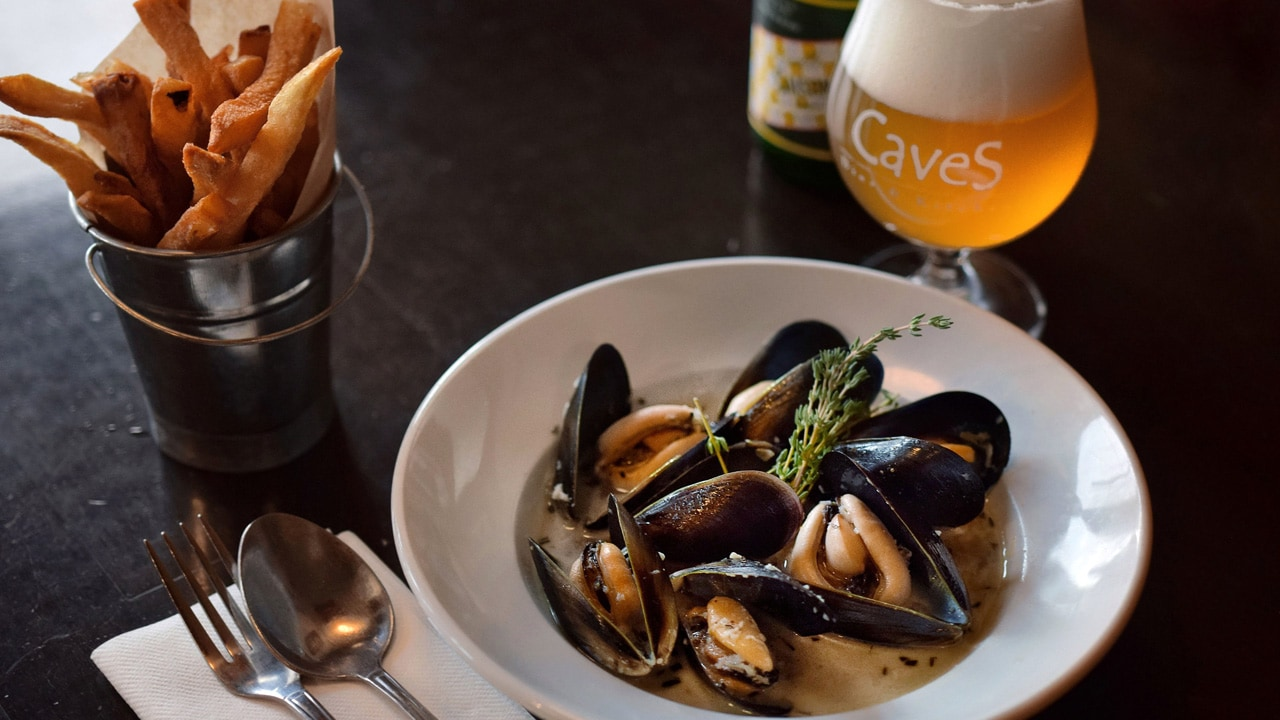 Meal of mussels, fries and a glass of beer.