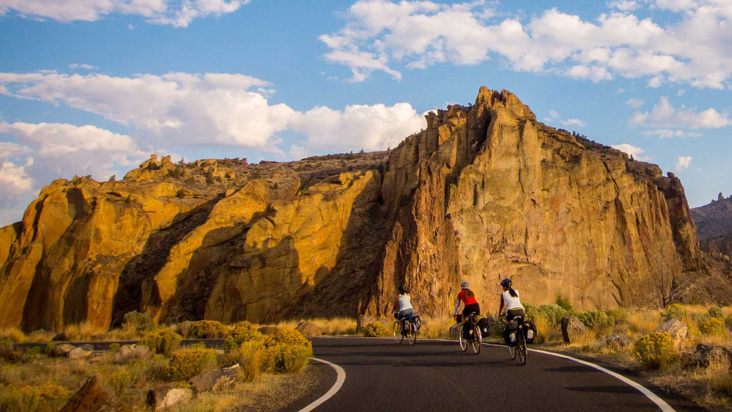 Three cyclists bike towards the famed Smith Rock State Park.