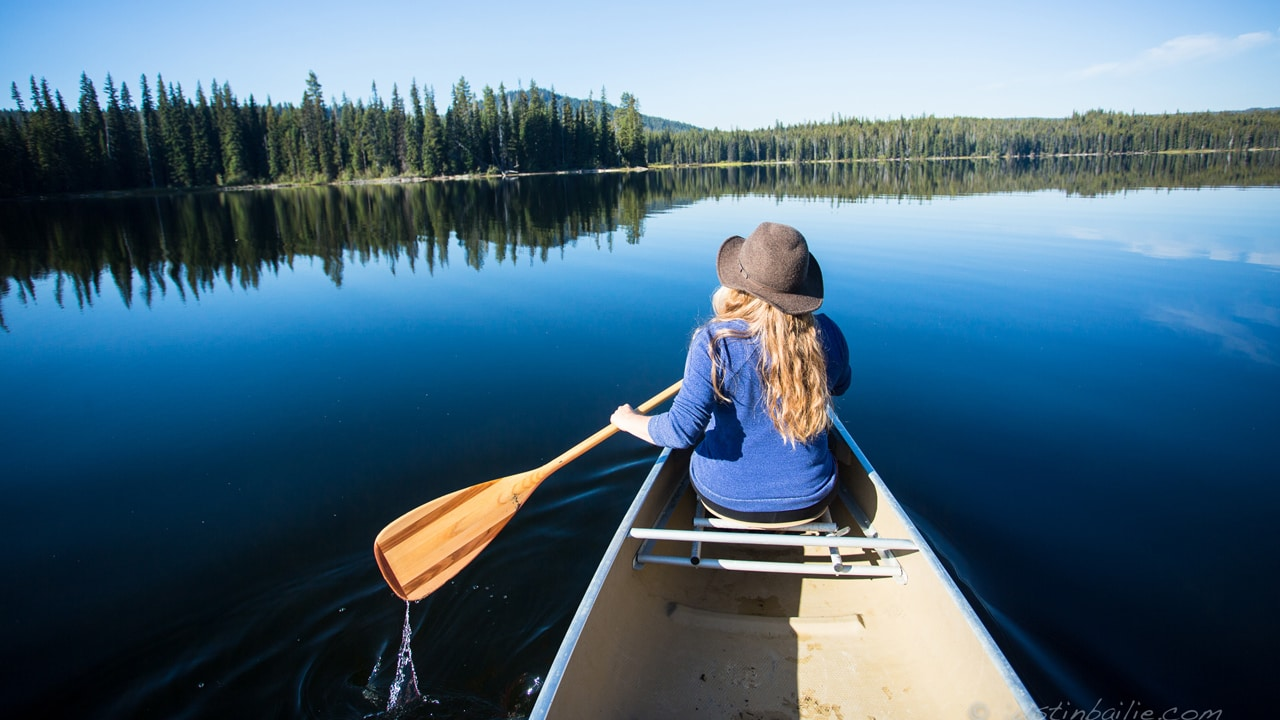 A woman paddles a canoe on a glassy blue lake.