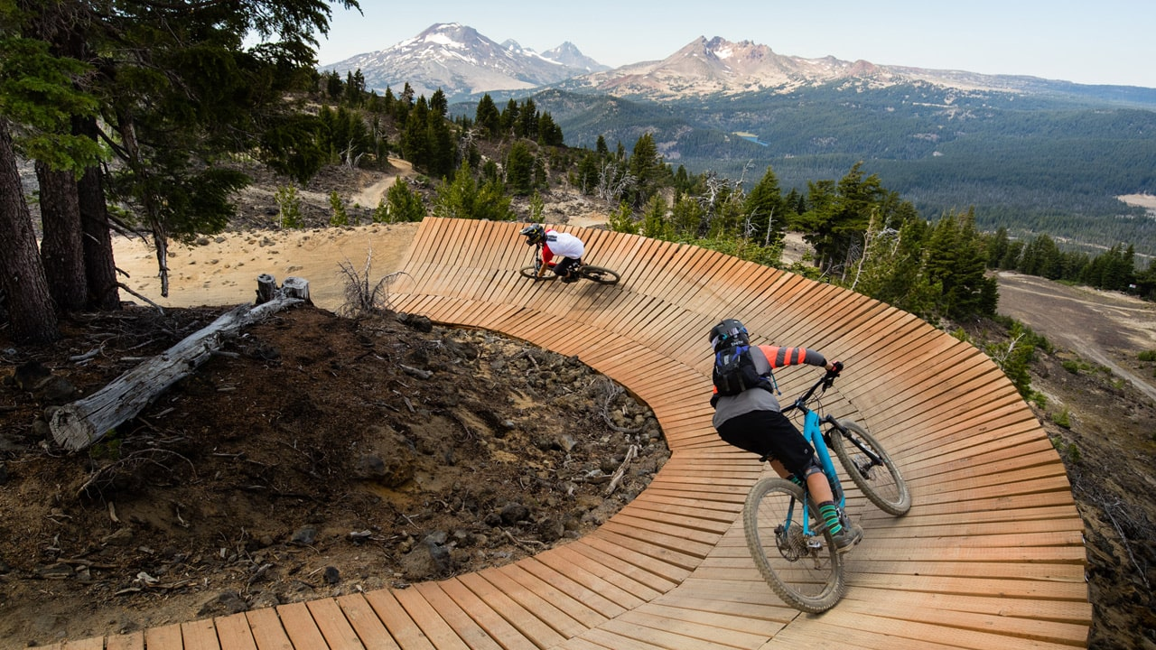 Mountain bikers pedal on the curved boardwalk trail at Mt. Bachelor.