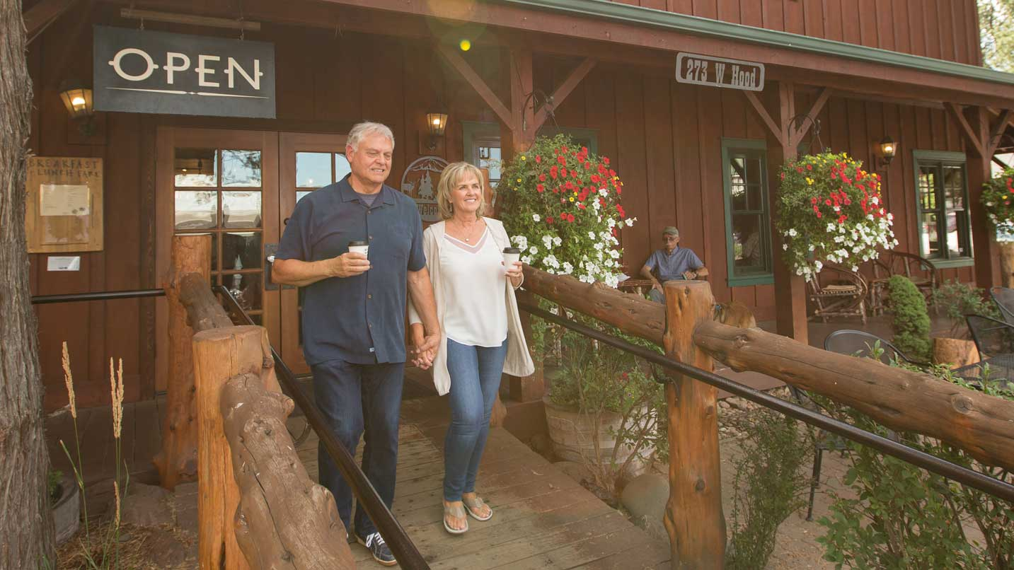 A couple holding coffee walks down a wooden walkway.