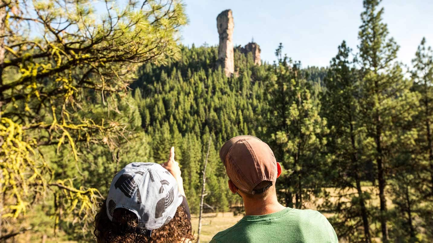 Two people look at Steins Pillar rising in the horizon.