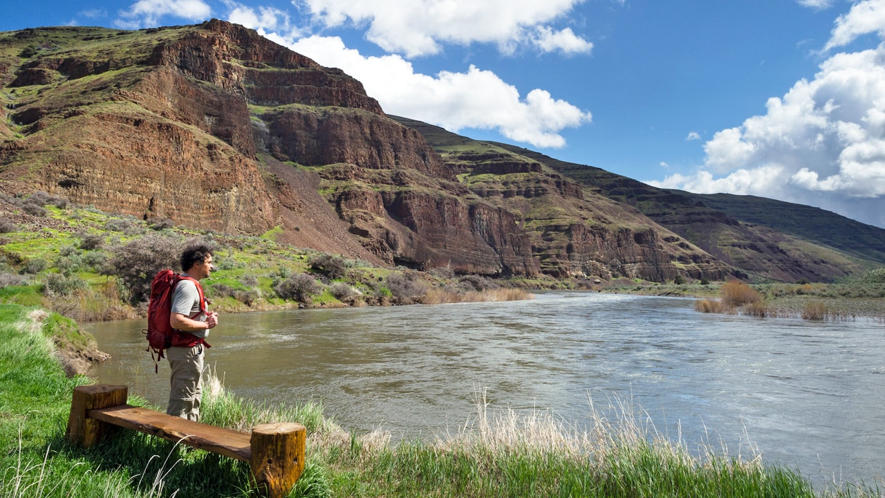 A backpacker looks out at the John Day River.