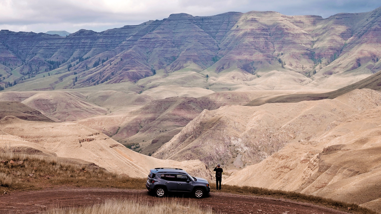 A person steps outside of their car to photograph Hells Canyon.