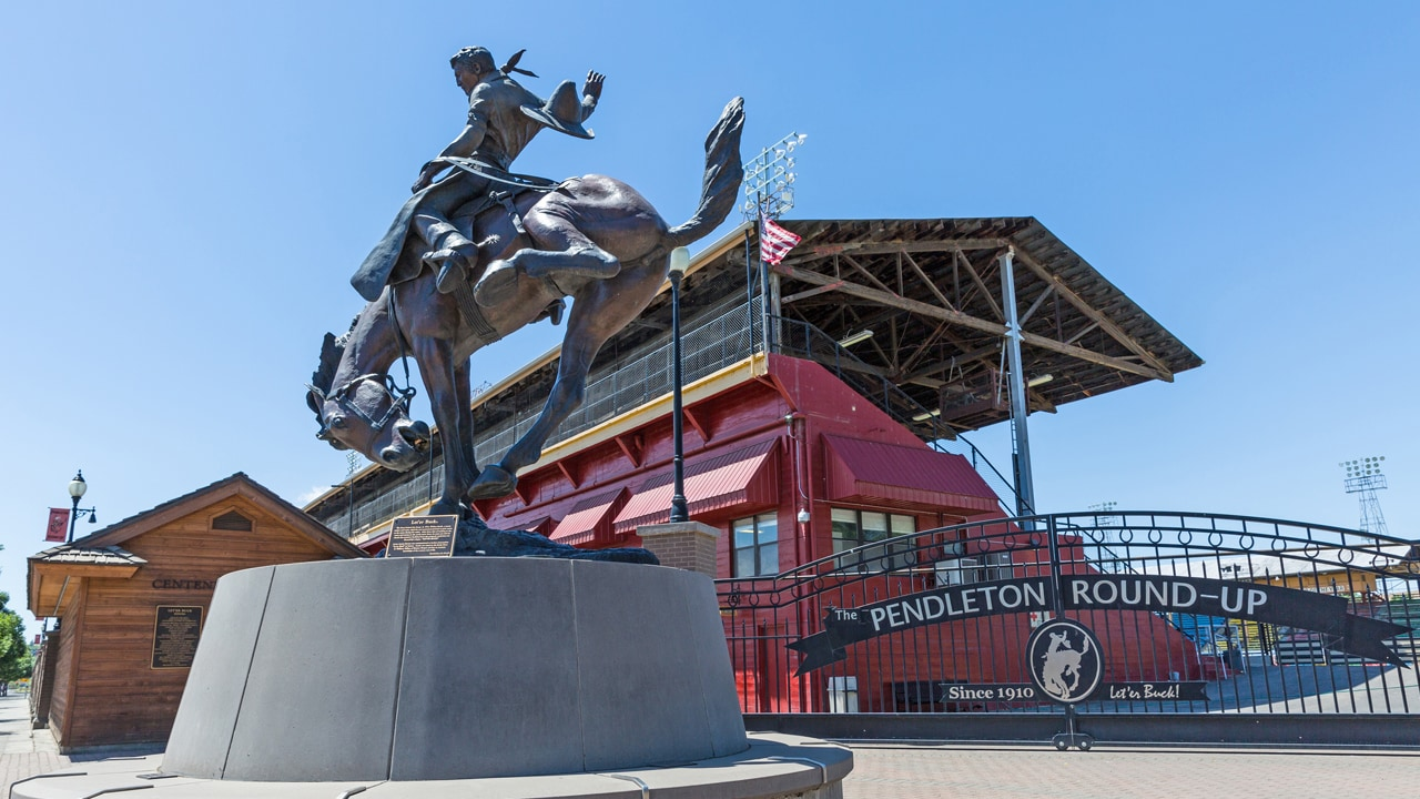 A bronze statue of a cowboy in front of the Pendleton Round-Up & Happy Canyon Hall of Fame.