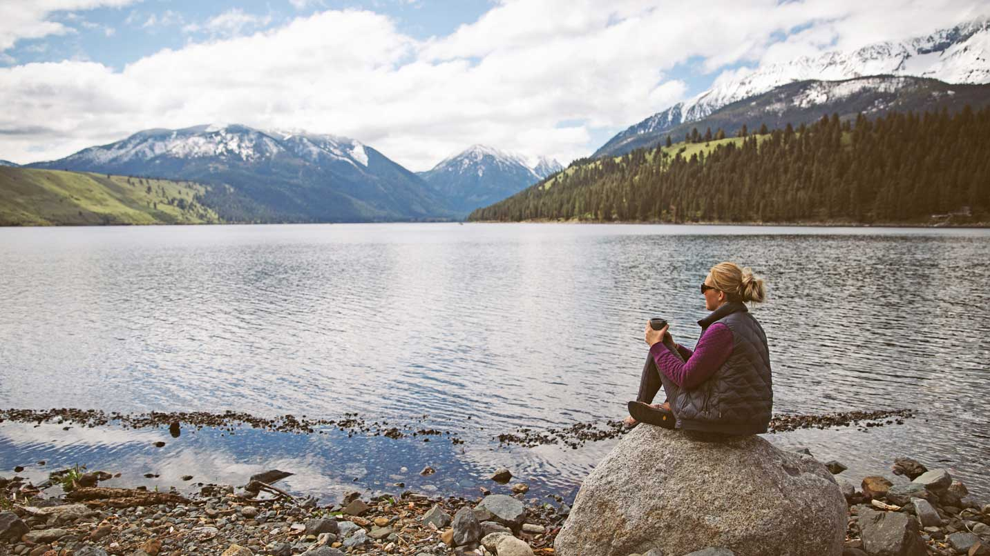 A woman sits with coffee at the shore of Wallowa Lake.