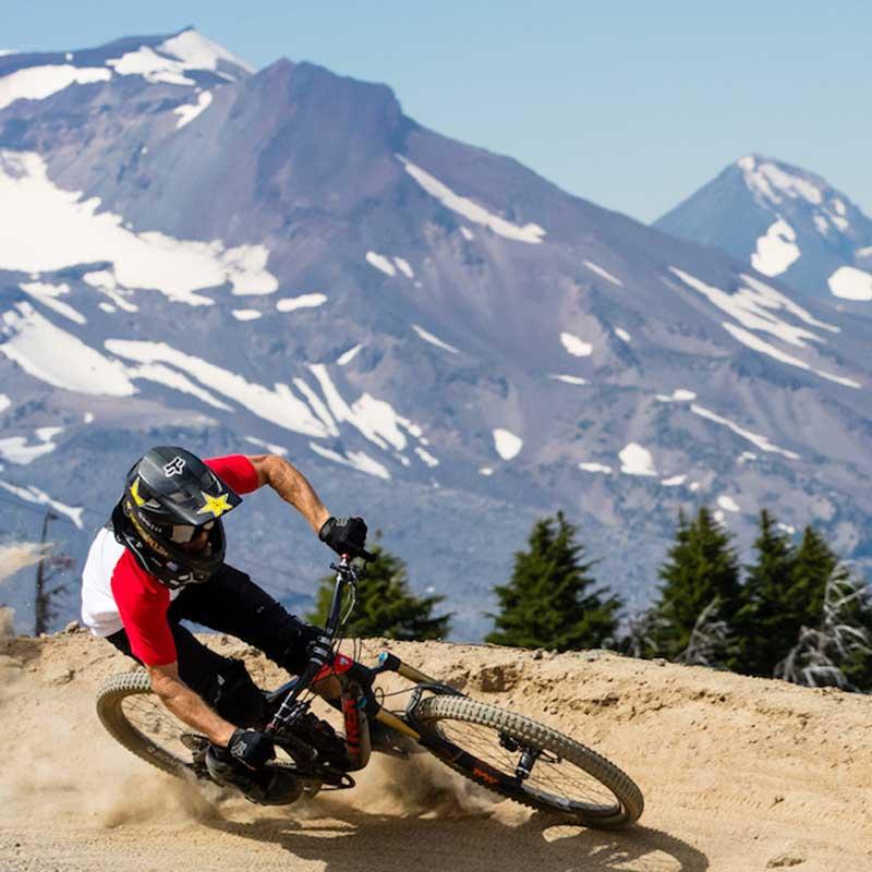 A mountain biker turns a corner in front of a snowy peak.
