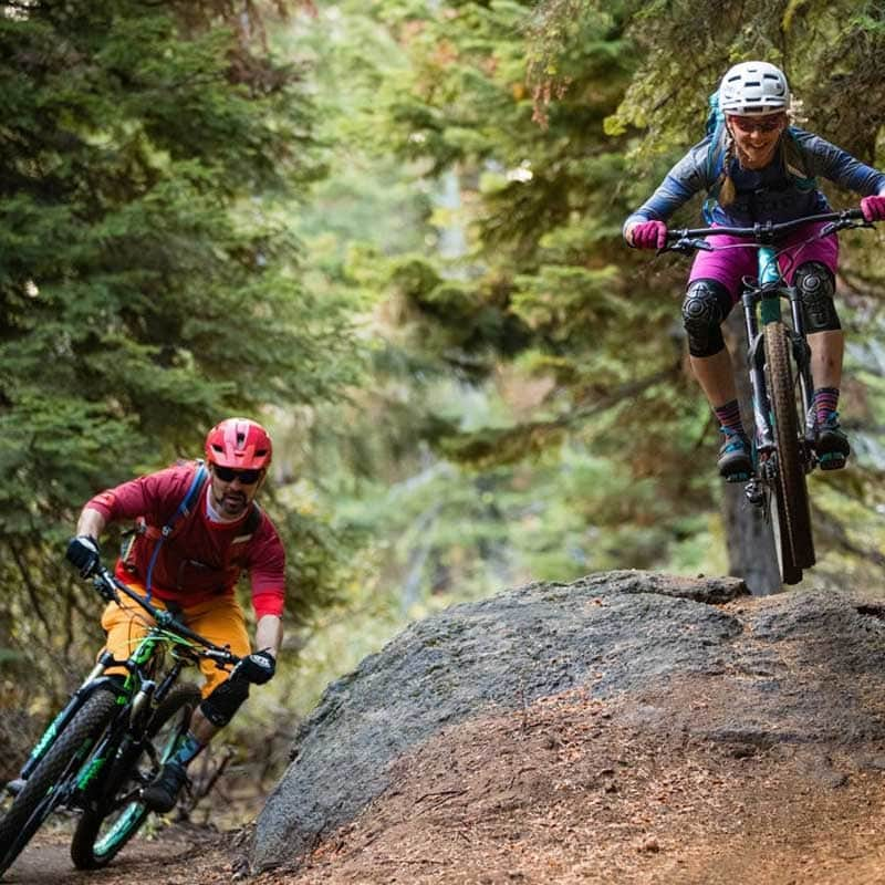Two mountain bikers smile as they take different sides of the dirt trail.