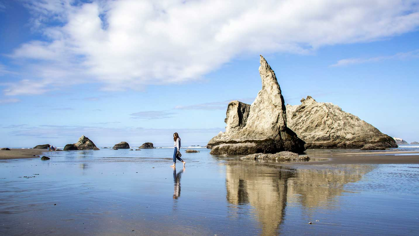 A person walks by the Howling Dog rock in Bandon.