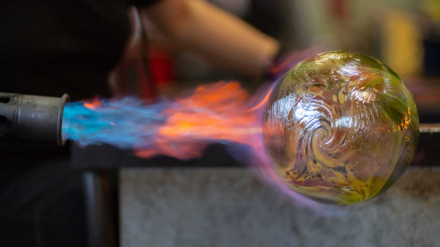 A glassblower adds heat to their creation.