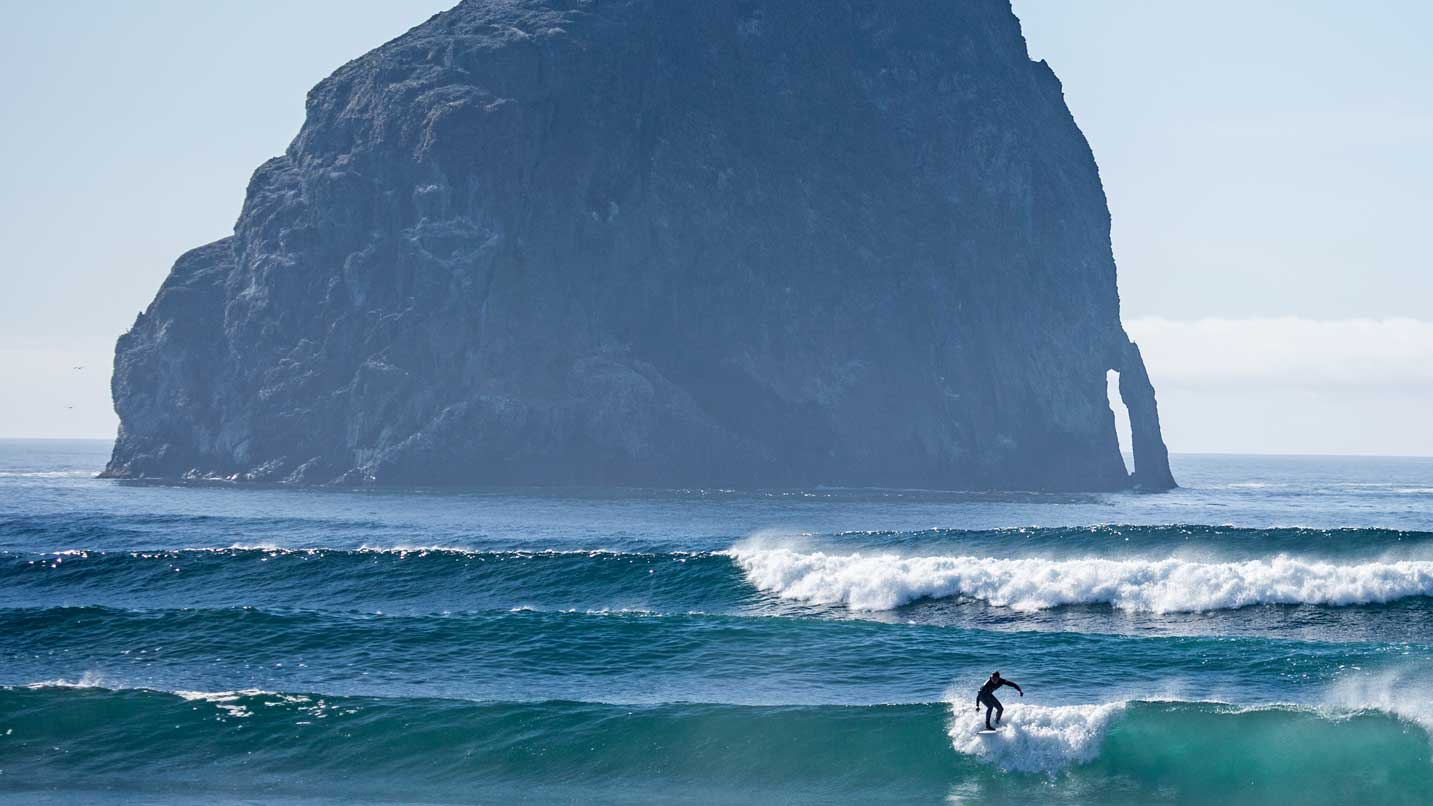 A surfer catches a wave in front of Haystack Rock in Pacific City.