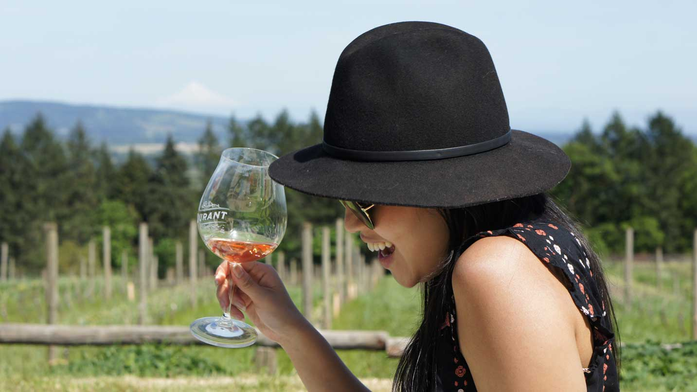 A woman smiles with a glass of rose in hand.