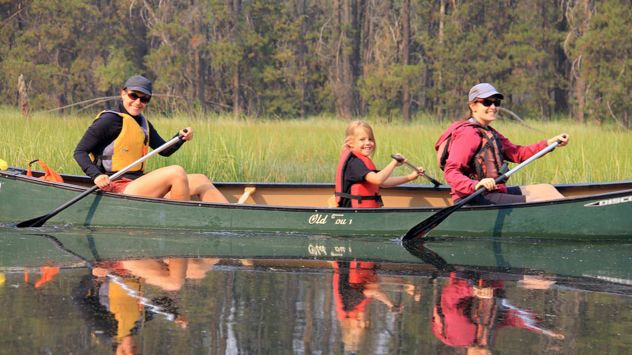 Two adults and a child smile from a canoe.