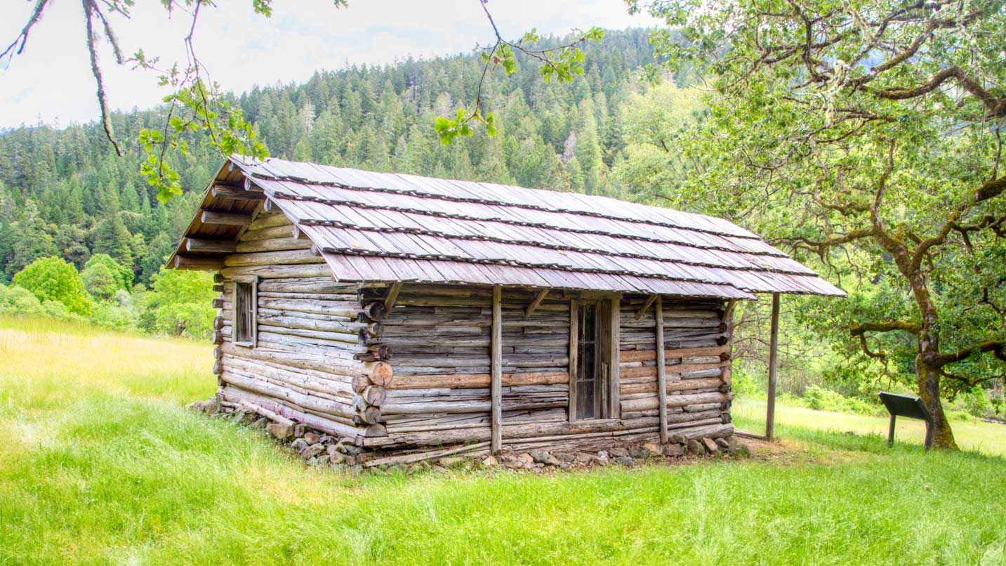 A rustic log cabin rests on a grass field.