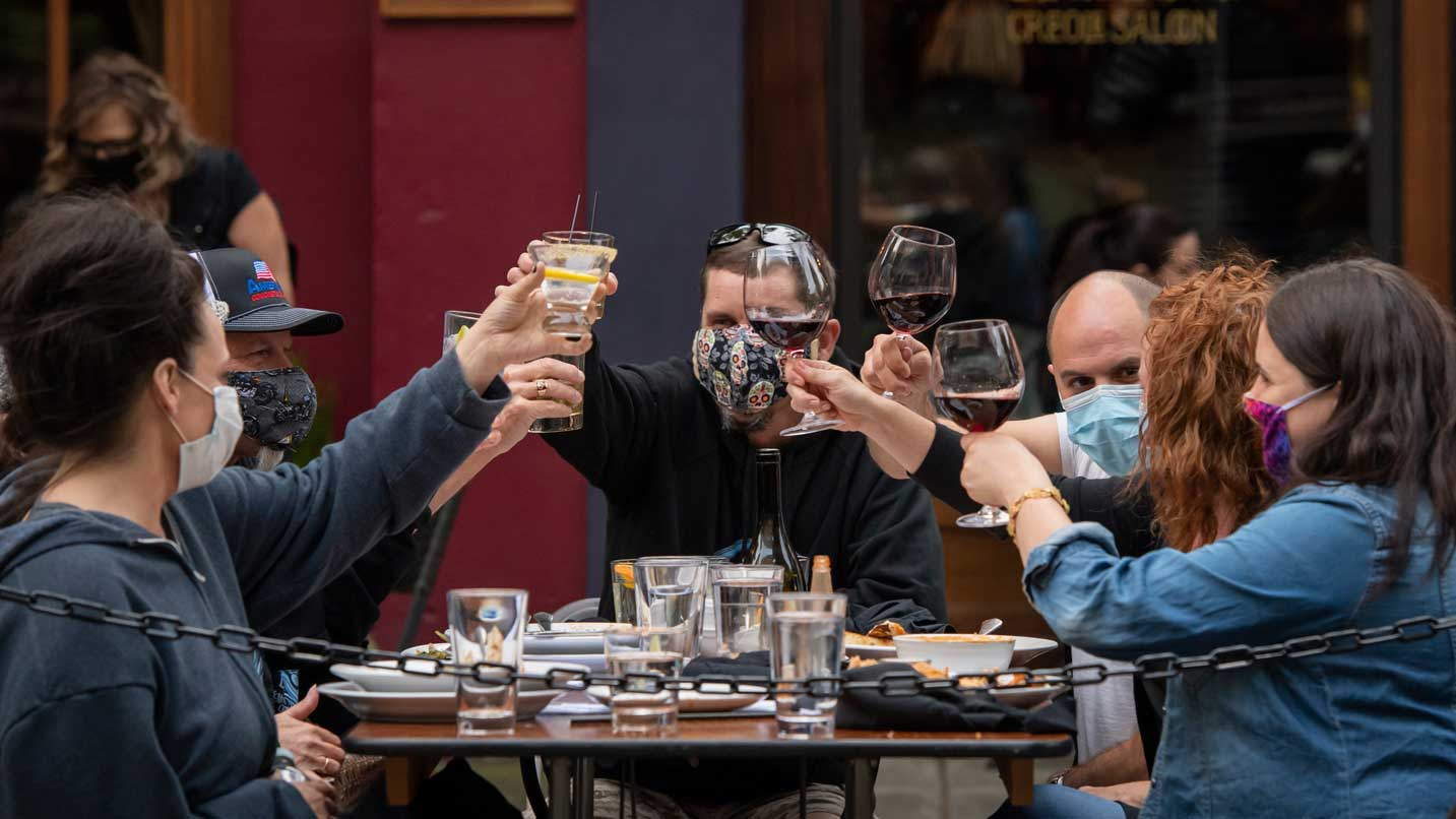 Friends wearing face coverings cheers their wine glasses.