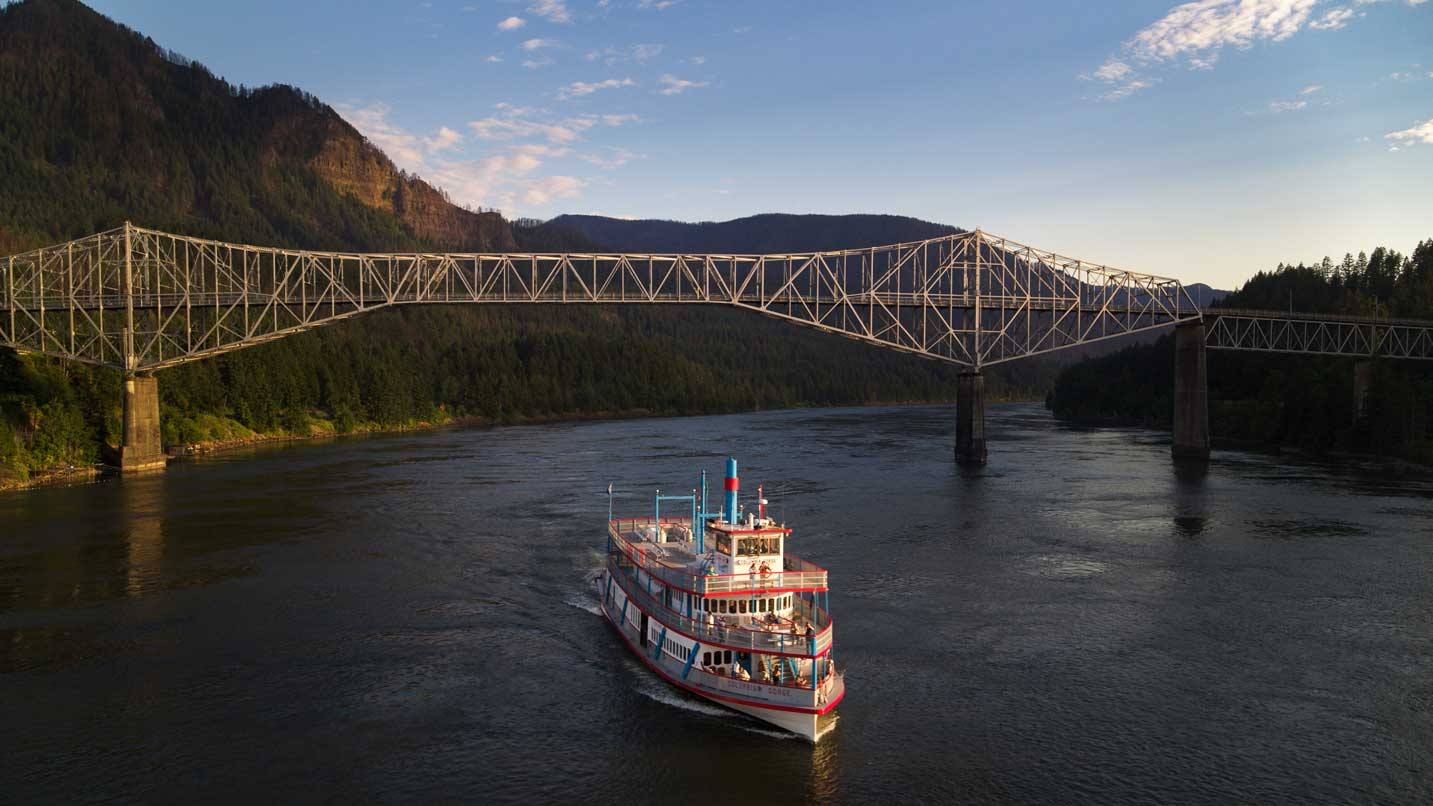 The red-and-white Columbia Gorge Sternwheeler navigates under the steel Bridge of the Gods.