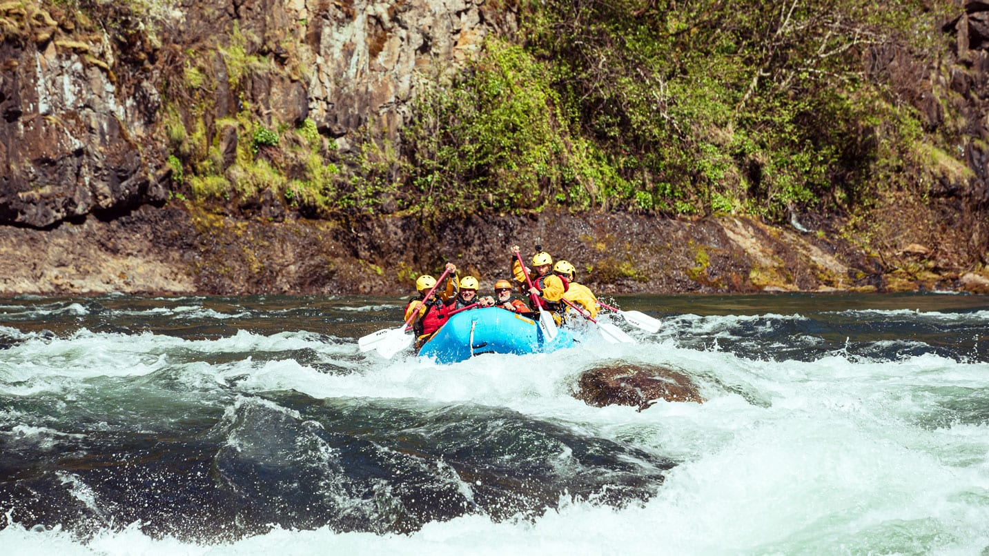 Rafters wearing helmets paddle down the rapids of the Clackamas River.