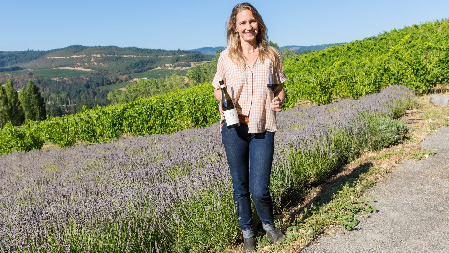 A smiling person holds wine in front of a lavender field.