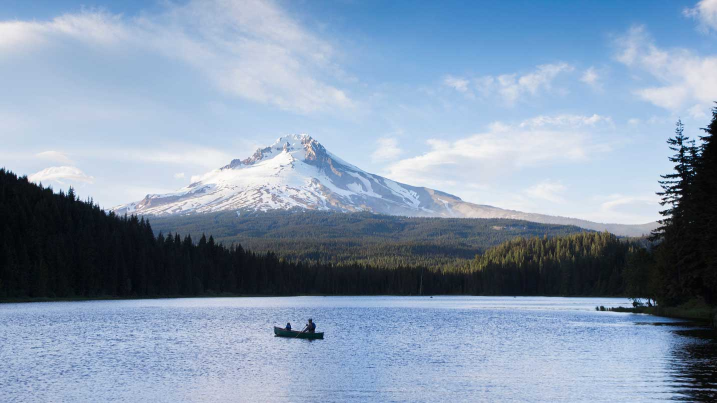 A canoe sits on the glassy waters of Trillium Lake with Mt. Hood's peak in the background.