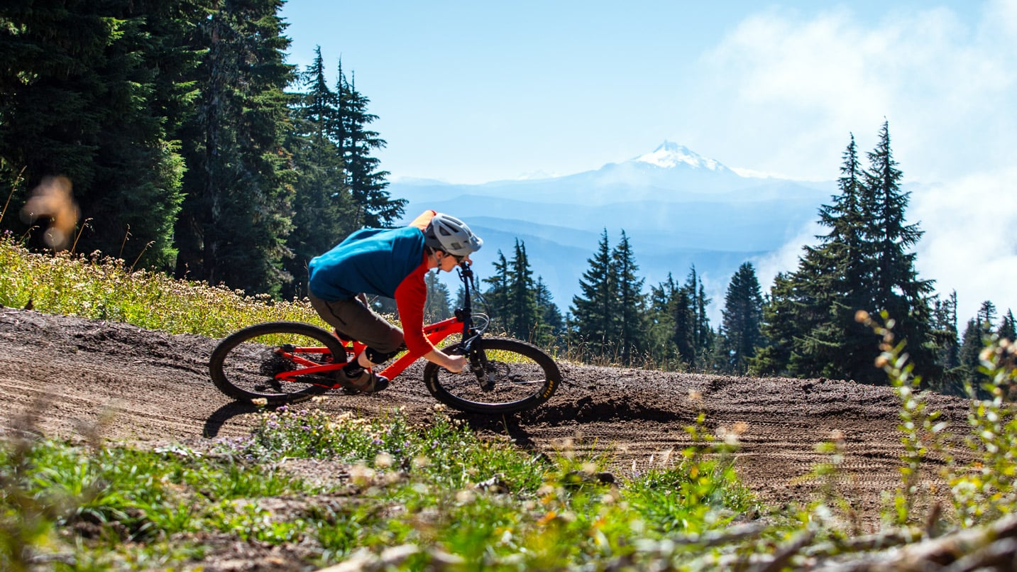 A mountain biker leans with a curve on a dirt track with Mt. Jefferson in the background.