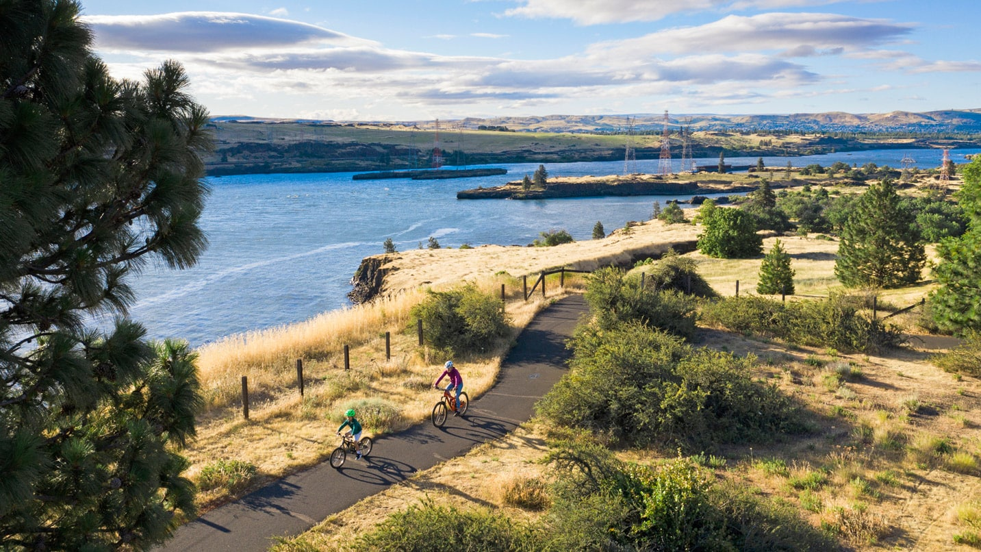 A bird's-eye view of cyclists pedaling on a paved path next to the Columbia River.