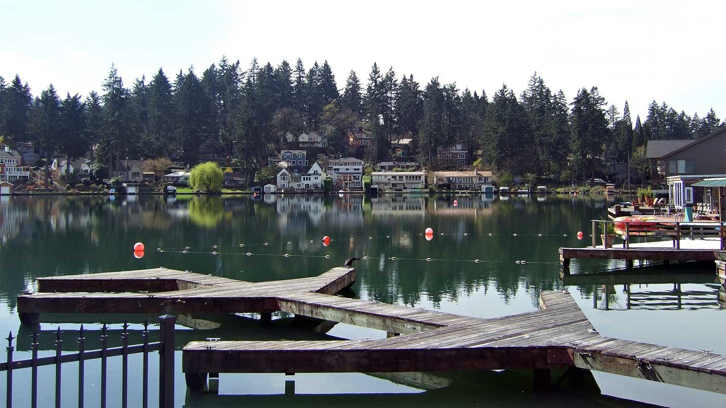 From a marina, waterfront houses reflect on Oswego Lake.