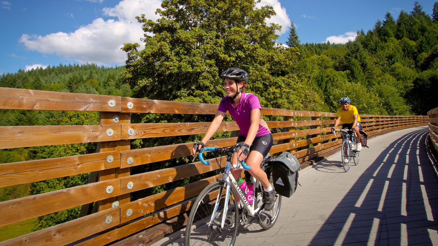 Cyclists smile as they pedal over the Banks-Vernonia State Trail's railway trestle.