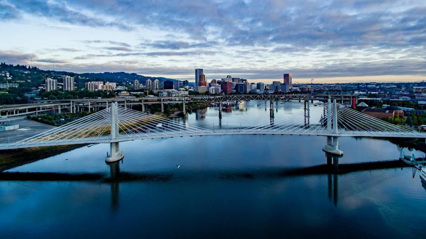 The car-free Tilikum Bridge spans over the blue waters of the Willamette River in Portland.