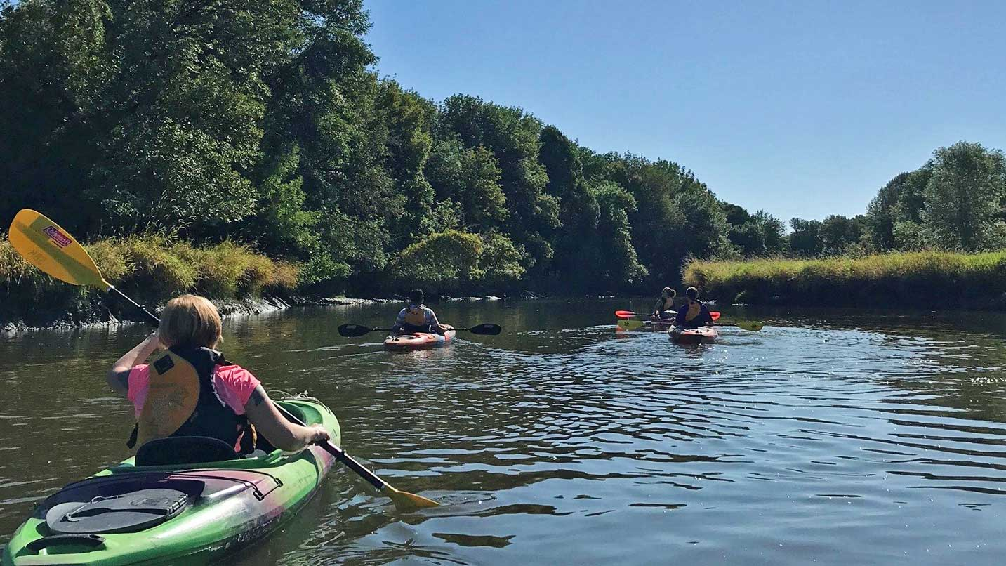 Kayakers paddle down the calm waters of Scappoose Bay.