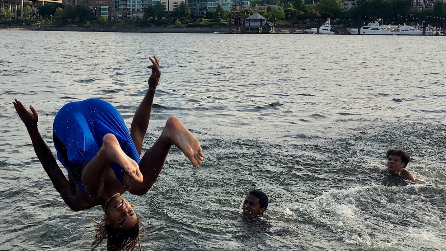 A young person backflips into the Willamette River as friends cheer them on.