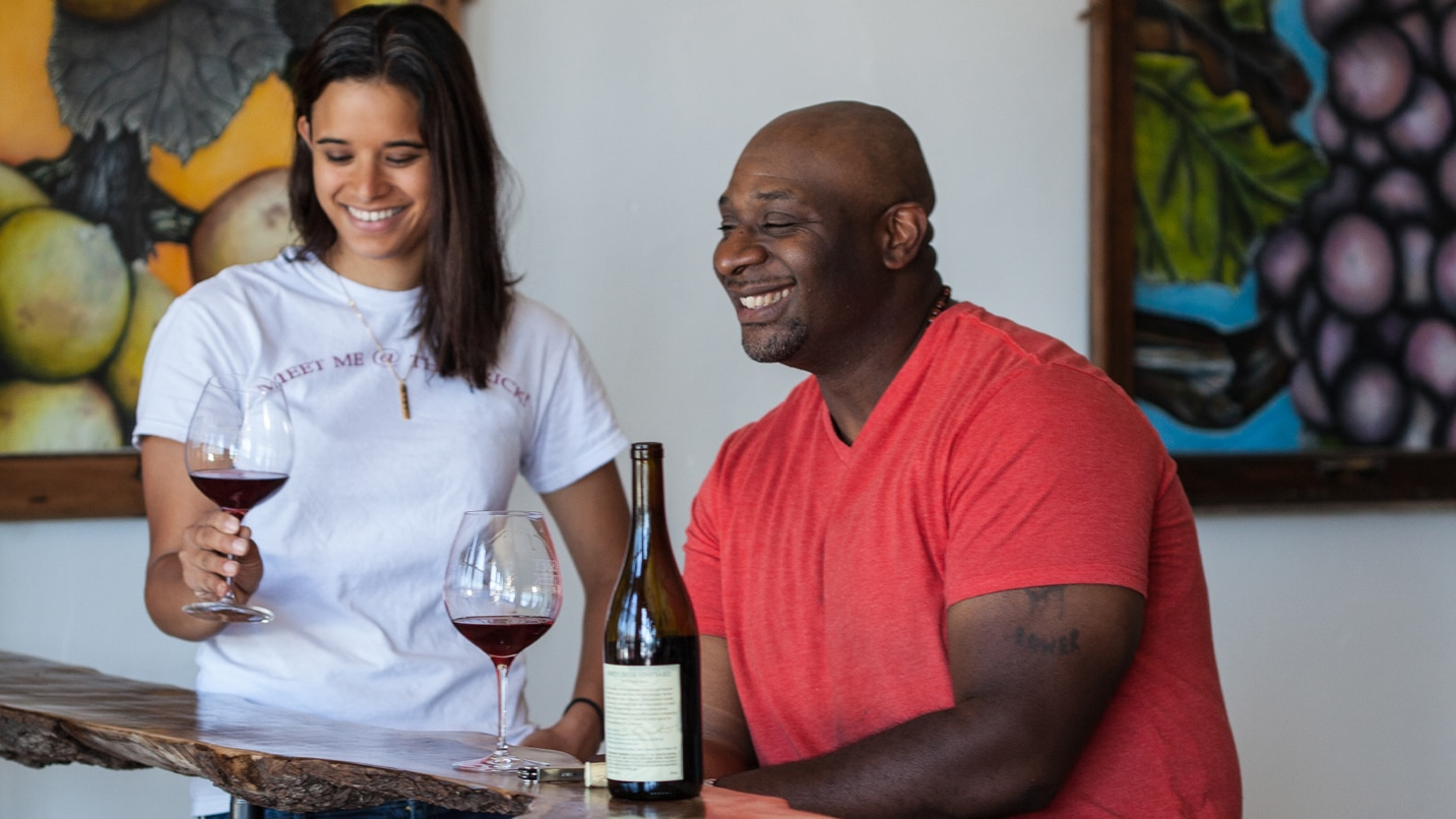 Bertony Faustin, Oregon's first recorded black winemaker, laughs with a guest in his tasting room.