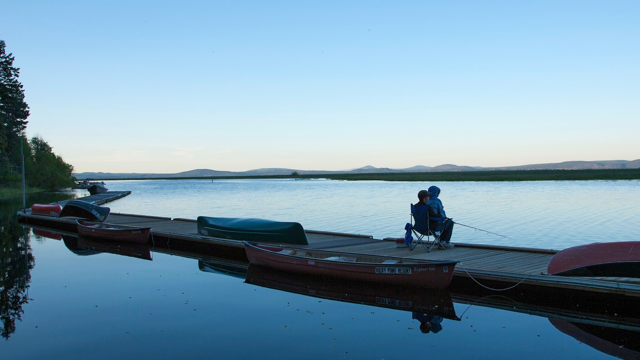 An angler sits on a deck at Upper Klamath Lake waiting for the fish to bite at dusk.