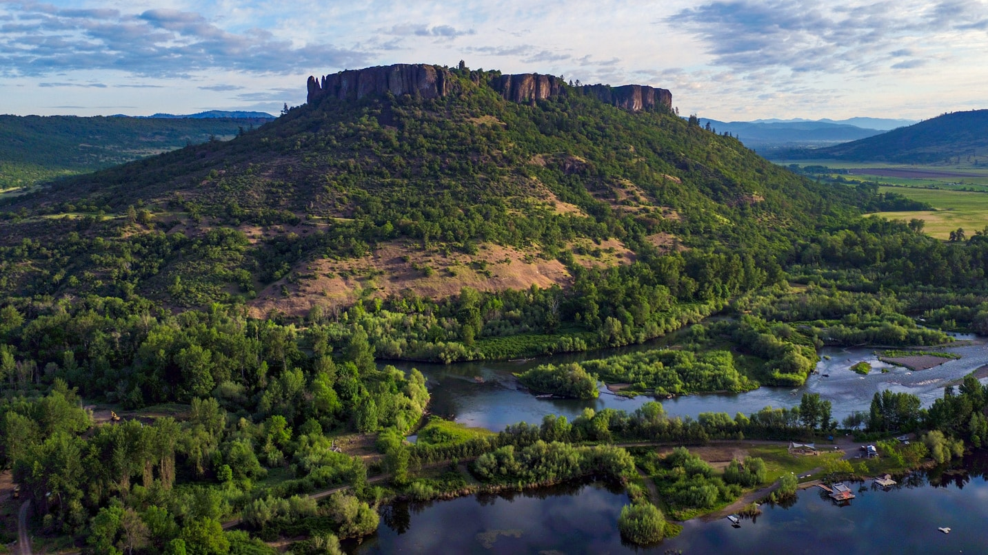 A volcanic plateau stands tall above green trees and a blue river.