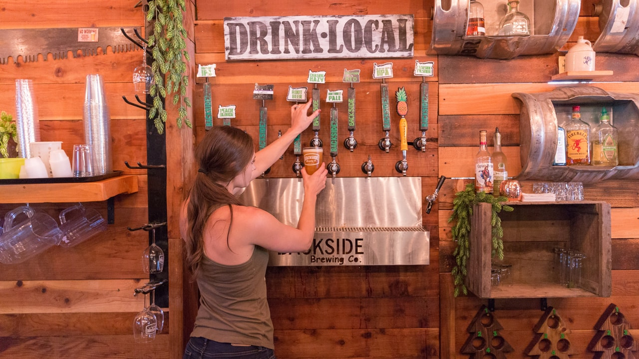 """A bartender pours from a tap in front of a """"Drink Local"""" sign."""