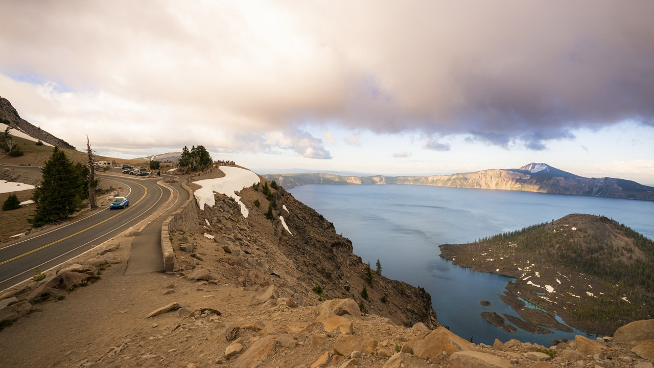 A car drives down Rim Drive where the road curves to an overlook above Wizard Island and Crater Lake.