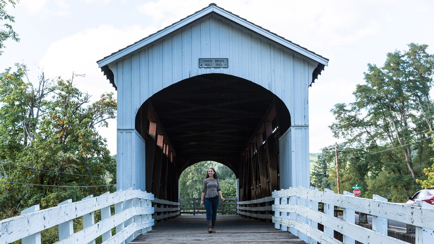 A person walks through the car-free covered bridge.