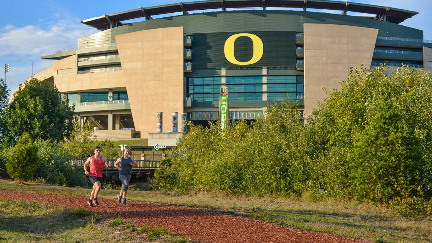 Two runners take Pre's Trail in front of the University of Oregon's Autzen Stadium.