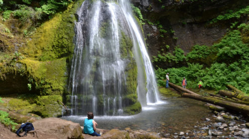 A hiker sits below the cascade of Spirit Falls, likely feeling the waterfall's mist.