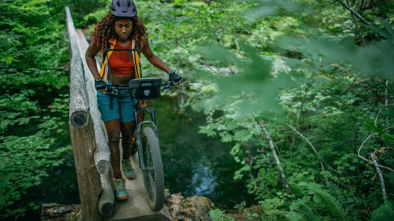 Analise walks her bike over a log bridge.