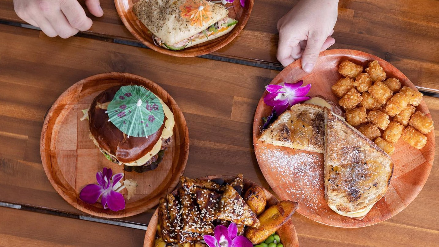 Plates of food with tiny umbrellas on an outdoor table
