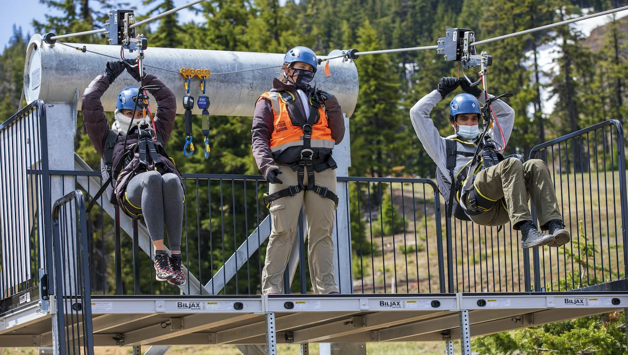 Two zipliners prepare for descent with an employee preparing them.