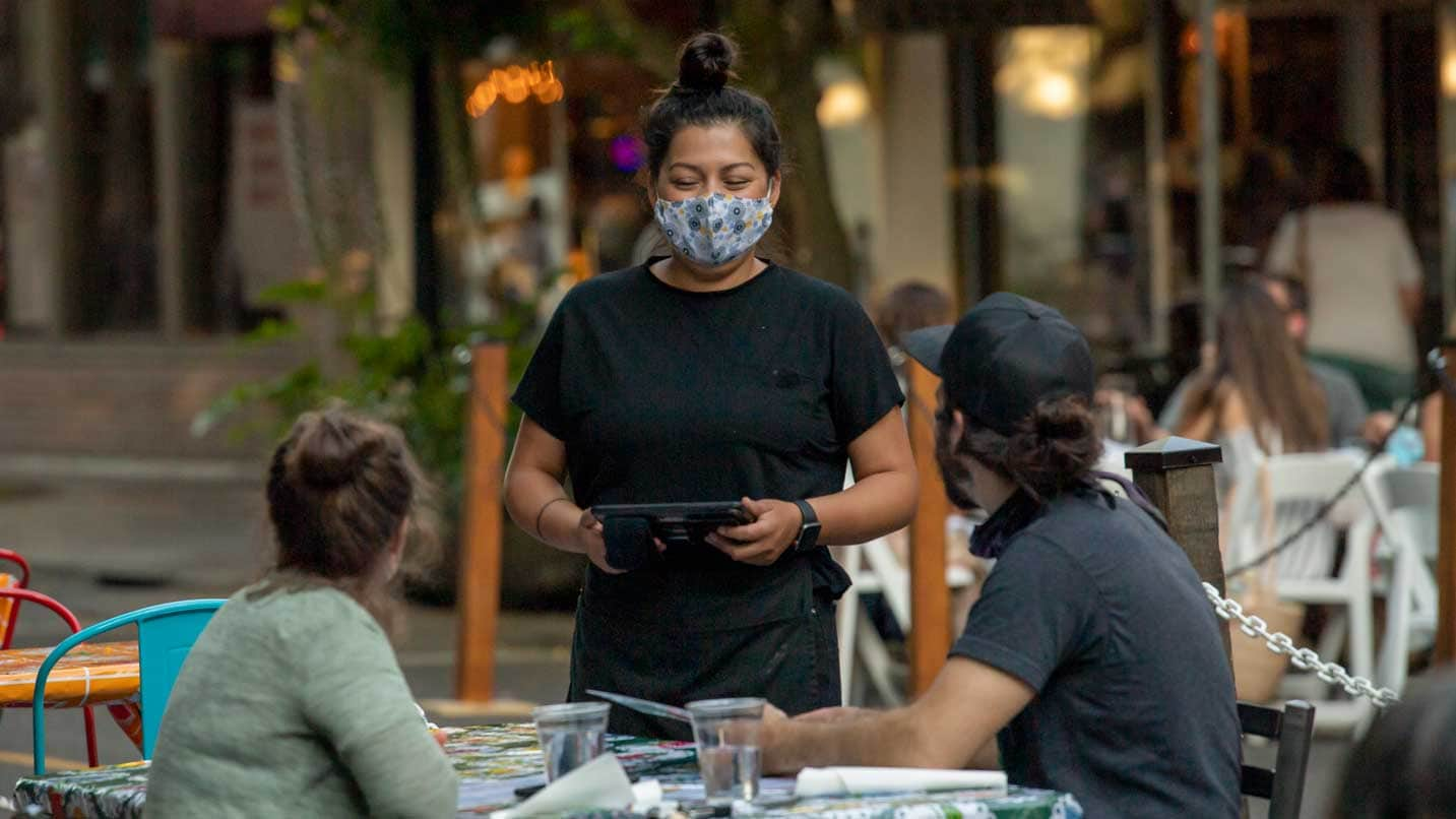 A waiter wears a face covering as they talk to patrons who are dining outside.