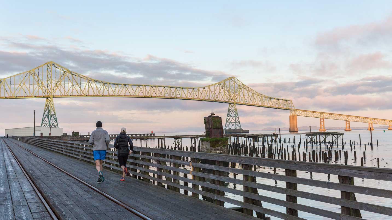 Two people run towards the Astoria-Megler Bridge at sunset.