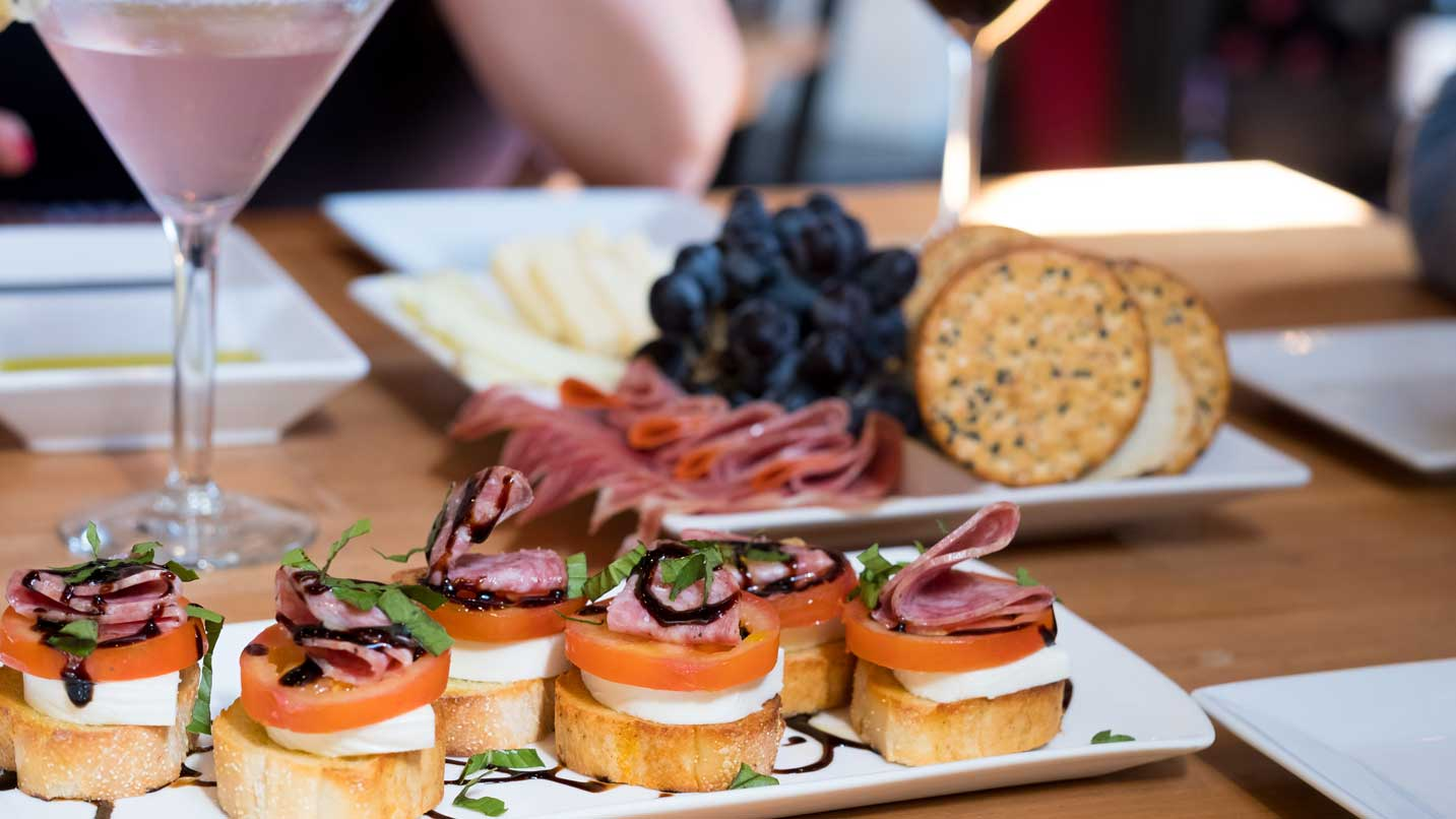 Plates of bruschetta and charcuterie sit in front of a lavender martini.