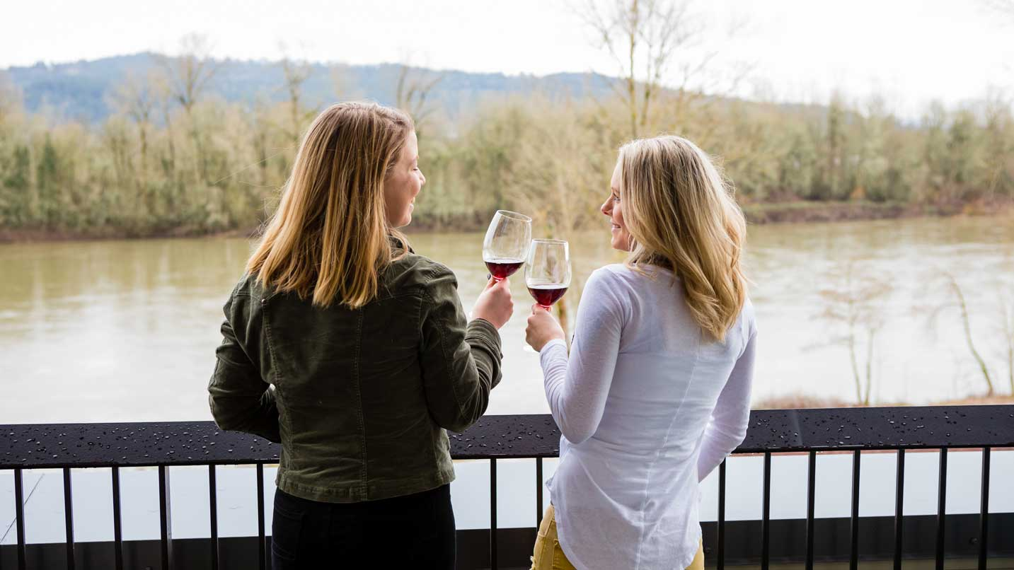 Two women cheers wine at a balcony overlooking a river.
