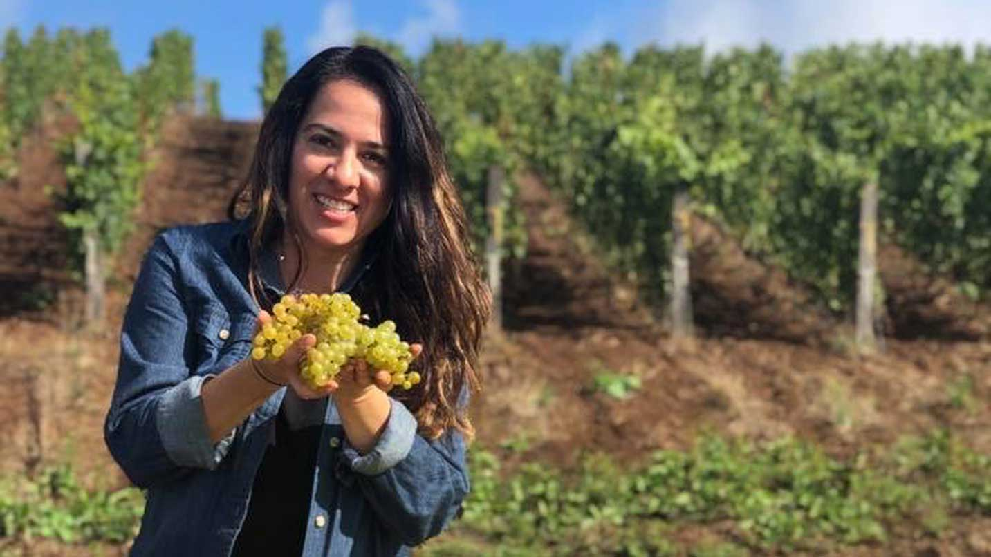 Cramoisi Vineyard's Sofía Torres-McKay holds wine grapes from a fresh harvest.
