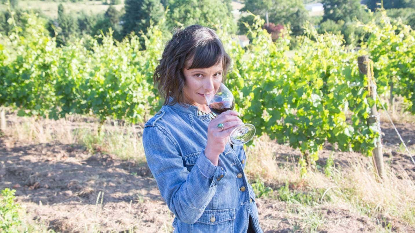Winemaker Cristina Gonzales smells a glass of red wine in a vineyard.