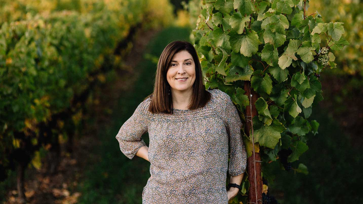 Carla Rodriguez of Beacon Hill Winery stands smiling in her vineyard during harvest season.