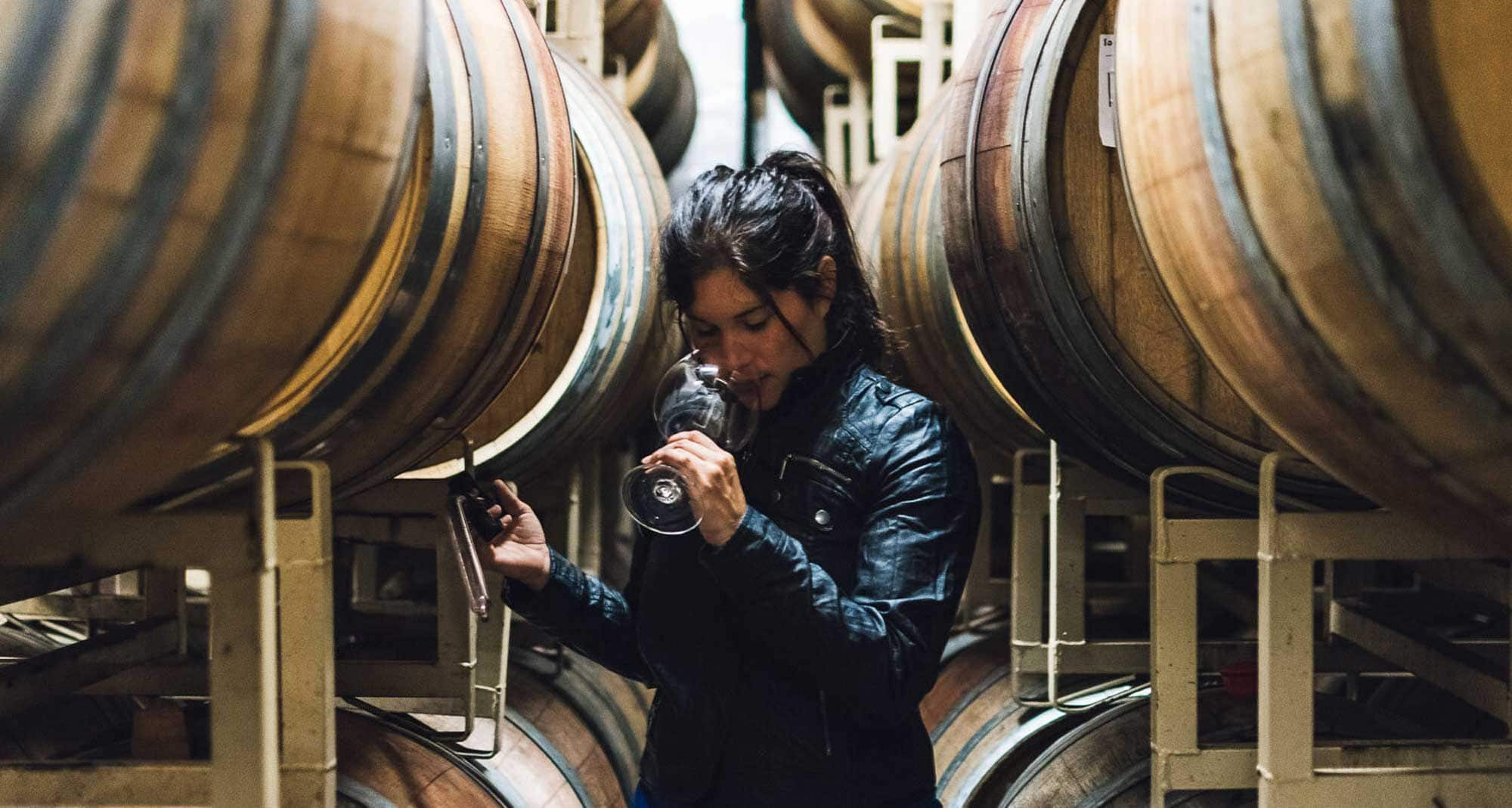 Aurora Cória smells a glass of wine while standing between barrels.