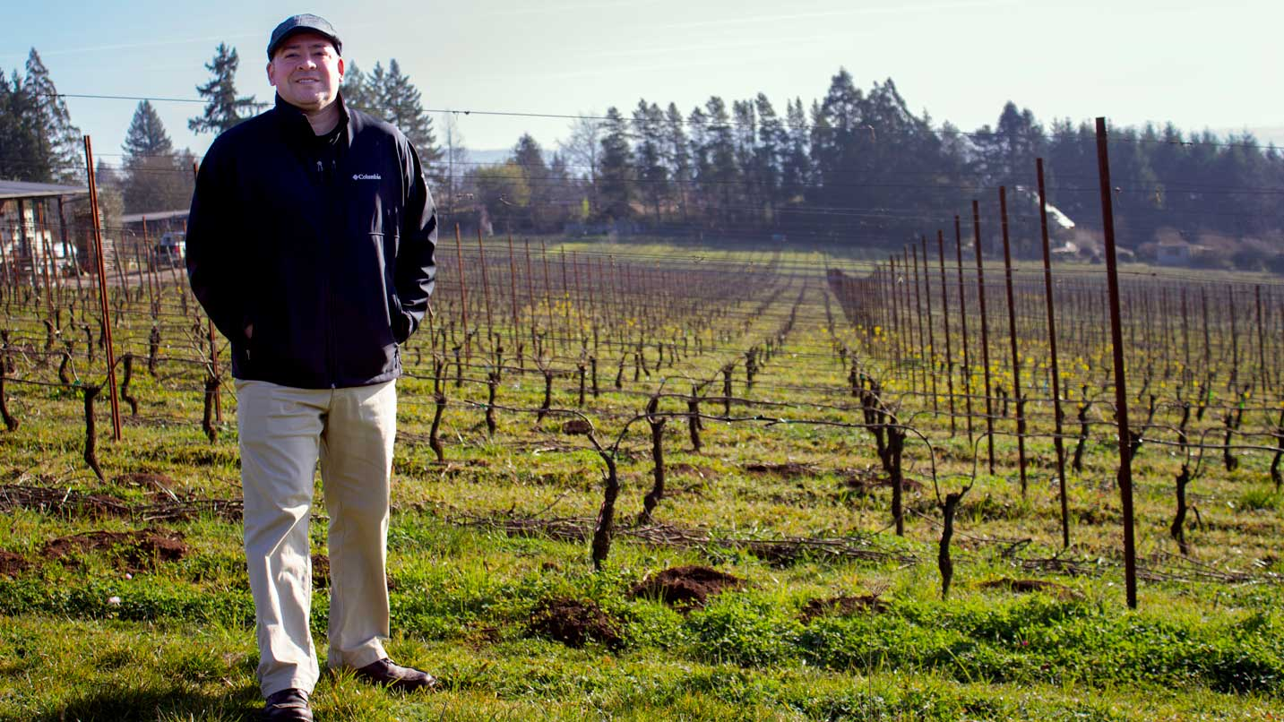 Sam Parra stands in a vineyard during the winter.